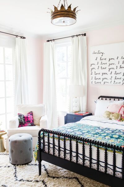 Kid's Room Inspiration: Girl's Bedroom that can work as a preteen bedroom! This space includes a black Jenny Lind spindle beframe, a gray tufted ottoman, a pink kilim cushion, and a white armchair.