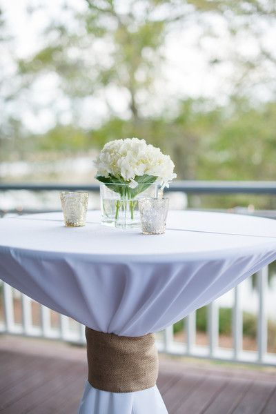 Cocktail tables with white linens, white hydrangeas, and votives. We love the rustic and nautical touch of the burlap ribbon {Alyona Photography}
