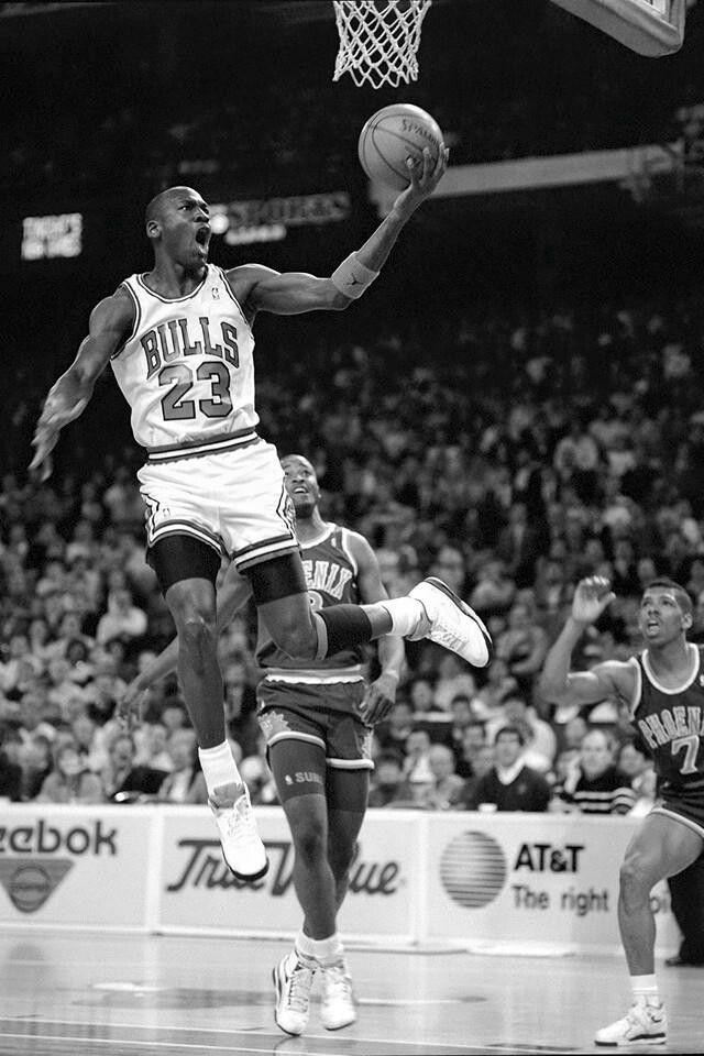 The GOAT dazzles the Suns' Kenny Battle and Kevin Johnson for a layup in Chicago.