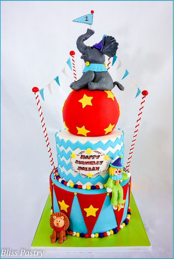 A circus 1st birthday cake featuring a happy clown, lion and elephant topper