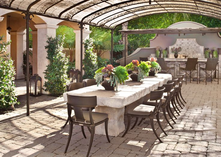 Outdoor Rooms - the long stone table under a shaded area that still allows sunlight in is perfect for the outdoor dinner party.