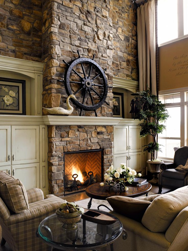 Comfy Living Room With Stone Wall, Stone Fireplace, And Cream Wood Mantle.  Ship Wheel On Mantle. Nice Design