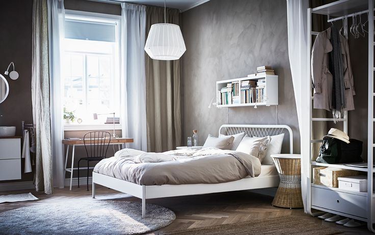 Scandinavian style bed and breakfast room with beige walls and white bed and wardrobe.