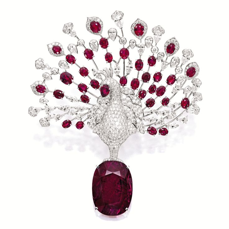 UNIQUE RUBY AND DIAMOND 'PEACOCK' BROOCH, CARTIER Modelled as a peacock, centring on a cushion-shaped ruby weighing 48.57 carats, displaying the plumage set with brilliant-cut, marquise- and pear-shaped rubies and diamonds together weighing approximately 28.00 carats, mounted in platinum, signed and numbered UF7936.