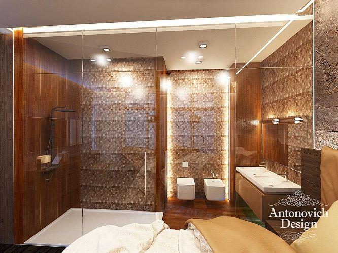 Ванную комнату и спальню разделяет прозрачная перегородка из стекла. Все стены и пол ванной выложены мозаичной плиткой теплого коричневого оттенка.