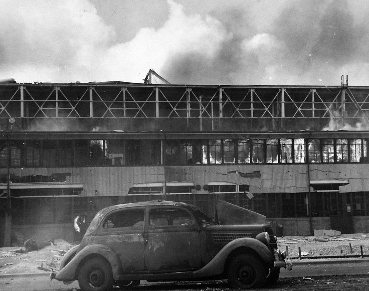 80-G-77652: Smoldering U.S. Navy Hangar at Naval Air Station, Kaneohe Bay, Oahu, after Japanese Attack on Pearl Harbor, December 7, 1941. Note, the wrecked automobile.