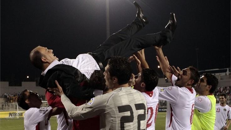 Jordan team'splayers celebrating with their coach Adnan Hamad