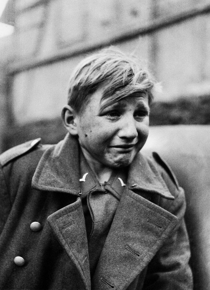 A fifteen year old German soldier, Hans-Georg Henke, cries after being captured by the US 9th Army in Rechtenbach, Germany, on April 3, 1945. He was a member of the Luftwaffe anti-air squad (Flakhelfer) who burst into tears as his world crumbled around him. His father died 1938 and his mother in 1944. He joined the Luftwaffe to support himself.