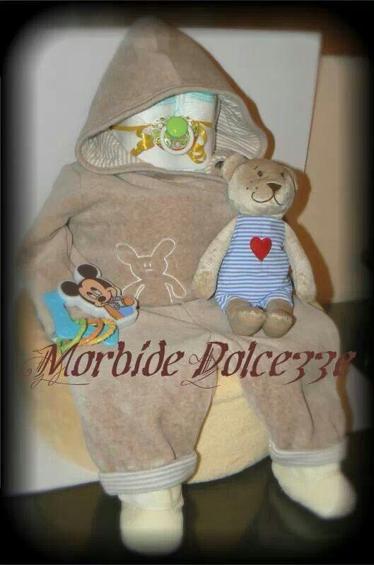 Tanti pannolini per questo bimbo seduto su base di pannolini e coperta felpata. Tutina in ciniglia, sonaglino,pupazzino e ciuccio decorativo.