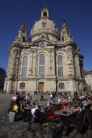 Touristen in einem Straßencafé auf dem Neumarkt vor der Frauenkirche in Dresden