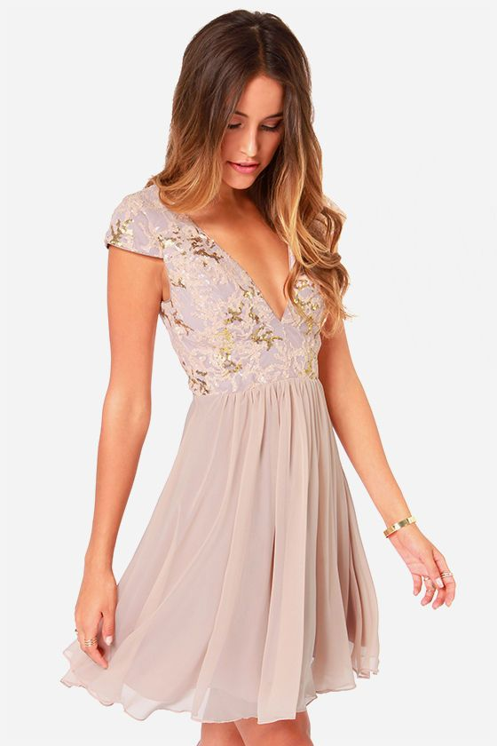 The perfect night can last forever in something as stunning as the Bariano Sabina Beige Sequin Dress! Gold and blush sequins dazzle over a tulle bodice, lined in smooth satin, while cap sleeves and a deep V neckline (with padded cups) give the perfect shape to this effervescent dress. A full skirt in beige chiffon gathers at the waist, with two layers of satin and a layer of tulle underneath for the perfect amount of volume. Hidden side zipper/clasp closure. Full satin lining. Self: 100%…