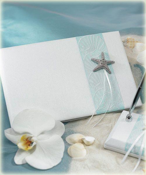 Gastenboek Seaside van wit satijn, blauwe strook met schelpen, een zeester en twee witte satijnen linten. Gastenboek Seaside van wit satijn met een licht blauwe strook met schelpen erop geborduurd, een grote zeester en twee witte satijnen linten.