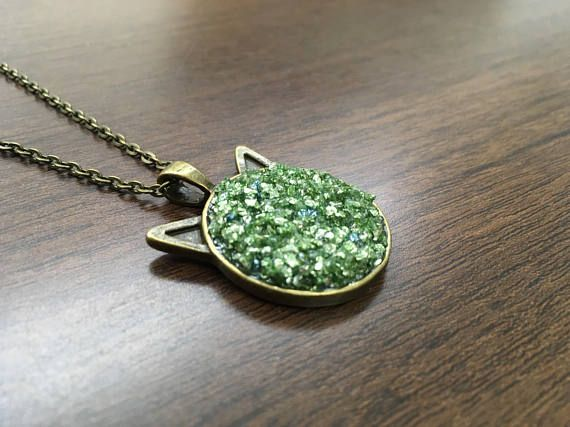 Made with glass glitter crystals and acrylic on a bronze pendant plate with cat ears. What you see is what you get, you'll be buying the necklace from the pictures. Pendant diameter:2.5cm Chain length:50cm