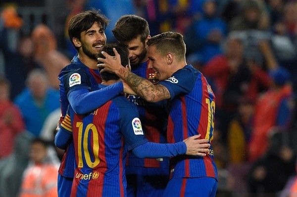 Barcelona's Portuguese midfielder Andre Gomes (L) celebrates with teammates after scoring a goal during the Spanish league football match FC Barcelona vs CA Osasuna at the Camp Nou stadium in Barcelona on April 26, 2017. / AFP PHOTO / LLUIS GENE