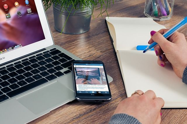 This image features a man writing on a notebook with a blue pen, a HTC lying on top of a Macbook at an office. Customize this great photo by putting your new app screenshot on the HTC area. How? Picapp.net is here for you. Go to Picapp.net, upload this great image, upload your app screenshot in the right area and you're done!  #HTC #picapp #office #desk #macbook #man