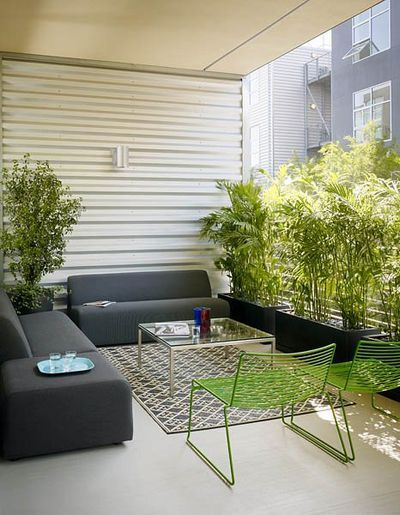 The couple's terrace has green Hee chairs from A+R, the  Laguna modular sofa from Room & Board and an outdoor rug from Potted.