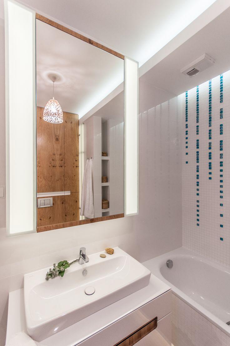 Biała łazienka ocieplona drewnem i turkusowymi szklanymi kroplami z mozaiki.