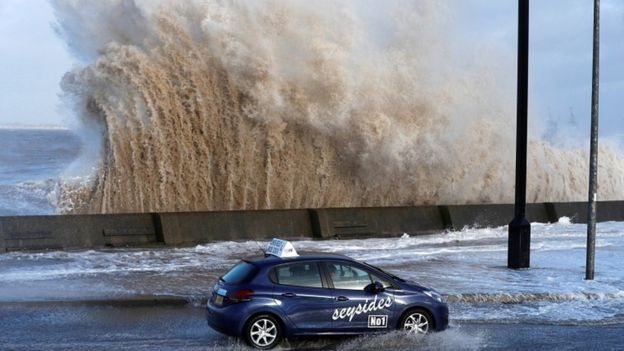 A car drives along a flooded road in New Brighton, on the coast of the Wirral peninsula, in Merseyside, Britain, January 3, 2018.