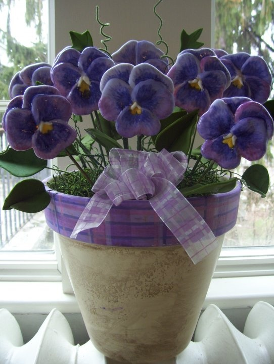 This pansy cookie arrangement was one of the first I designed. There is an incredible amount of detail I hand paint with food coloring. The leaves are edible gumpaste and I handpaint the design on the clay pot.  This arrangement has 12 cookies and sells for $85.00
