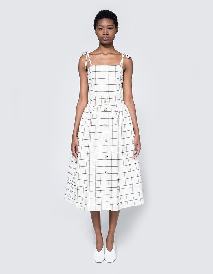 Dress from Rejina Pyo in Mix Check. Square neckline. Thin straps with tie adjustment. Concealed back zip closure. Darts at bust. Dropped waistline. Hidden on-seam side pockets. Full pleated skirt with button detailing. Lined. • Wool/silk blend shell, s