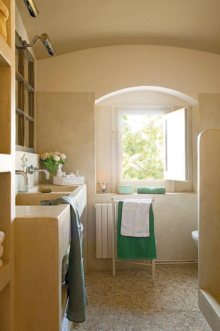 El lavamanos  Sobre el lavamanos doble, una ventana antigua comprada en una almoneda se ha transformado en un original espejo.