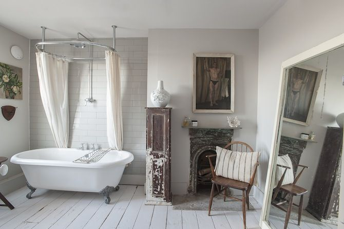 Superb white bathroom complete with roll-top bath and original fireplace.