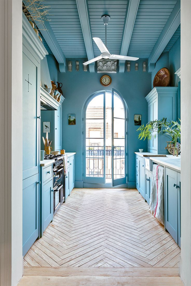 Stunning blue kitchen with chevron wood floor and arched floor to ceiling  window.