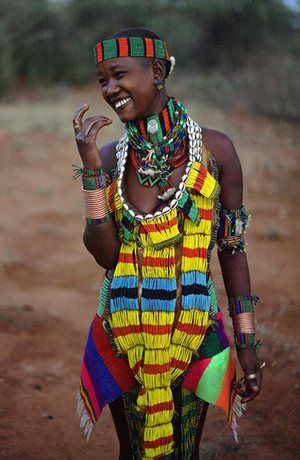 Tribes of Ethiopia - A woman from the Bena tribe eats honey collected from a tree