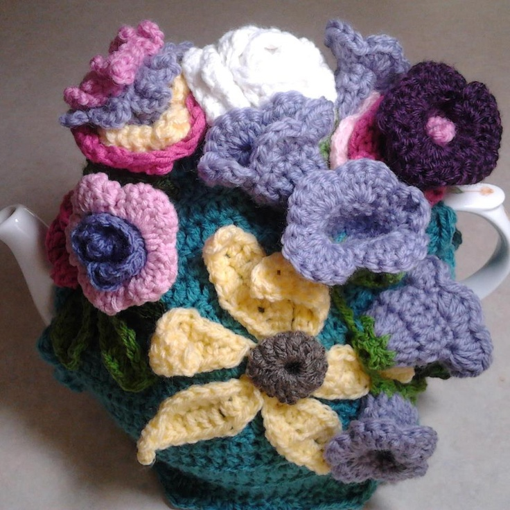 Teal crochet tea cosy with sunflower and violets