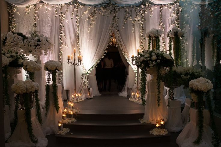 Conventino Ballroom entrance decorations, white tent and white mixed flowers in vase to decorate the stairs, altogether with candles