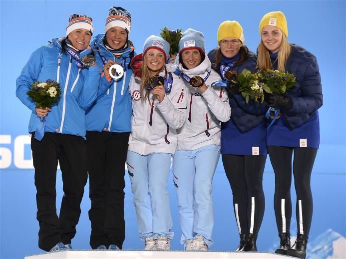 Silver medalists Aino-Kaisa Saarinen and Kerttu Niskanen of Finland, gold medalists Ingvild Flugstad Oestberg and Marit Bjoergen of Norway, and bronze medalists Ida Ingemarsdotter and Stina Nilsson of Sweden celebrate on the podium during the medal ceremony for the Cross-Country Ladies' Team Sprint on Day 14 of the Sochi 2014 Winter Olympics at Medals Plaza. Sochi 2014 Day 14 - Medals Ceremony.