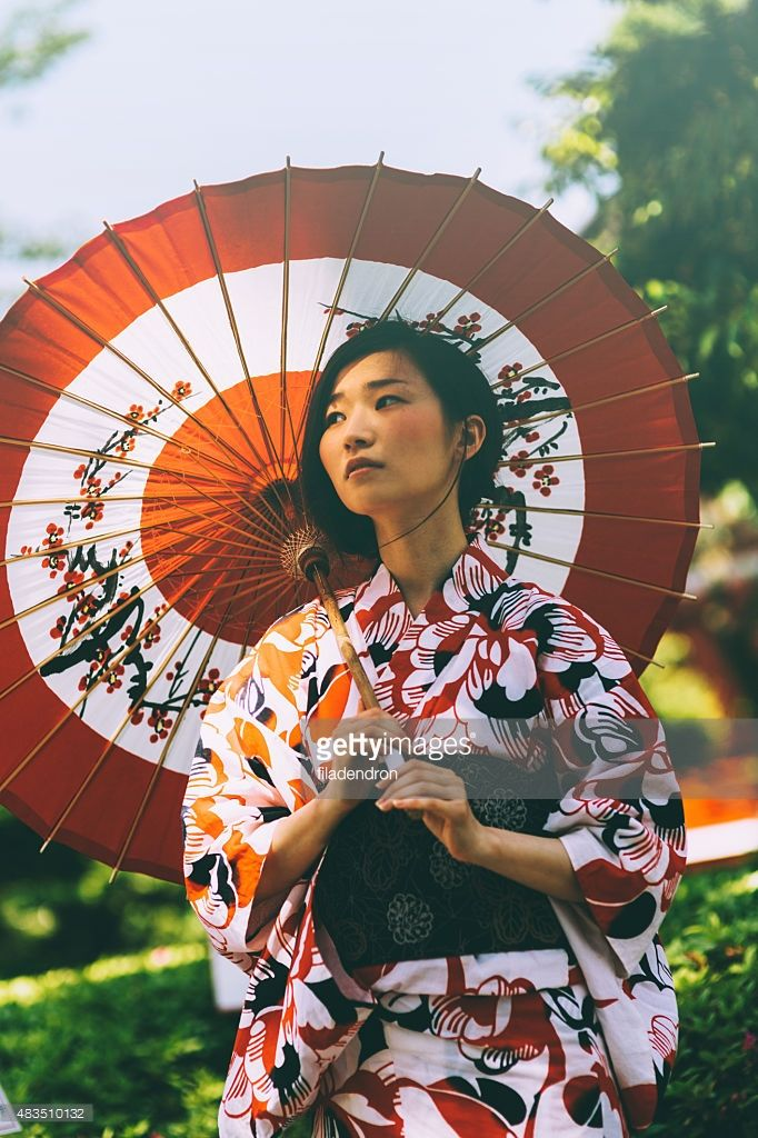 Beautiful japanese woman stand in the park. She wears kimono, obi and hold oil paper umbrella.The kimono is very colorful and elegant. She seems very pensive.