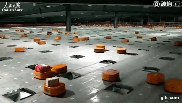 Robotic parcel sorting facility in China  The dumb robots fall into the holes while the smarter ones survive and breed.    From the YouTube description:  Chinese delivery firm is moving to embrace automation.  Orange robots at the company's sorting stations are able to identify the destination of a package through a code-scan virtually eliminating sorting mistakes.  Shentong's army of robots can sort up to 200000 packages a day and are self-charging meaning they are operational 24/7.  The…