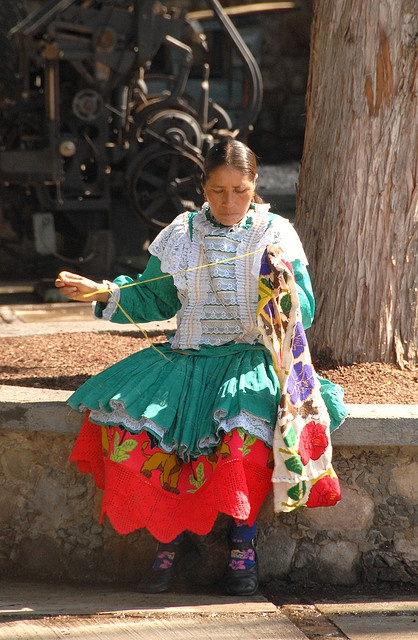 A Mazahua woman in traditonal dress embroiders fabric that will become the hem of a skirt. Zitacuaro, Michoacan Mexico