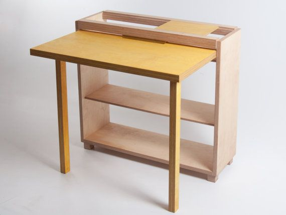 Escritorio abatible Tablet  Una mesa abatible con doblar las piernas magnéticas y un sistema modular de la tableta. Elaborado a partir de FSC certificada la madera contrachapada de abedul sólida.  Aparentemente simple y adaptable sin fin, la mesa de la tableta de Bee9 está diseñada para redefinir donde usted puede poner un escritorio. Por ser frugal en su uso del material y espacio, escritorio / mesa de centro hace un uso óptimo de espacio limitado.  La primera pieza de mobiliario utiliz...