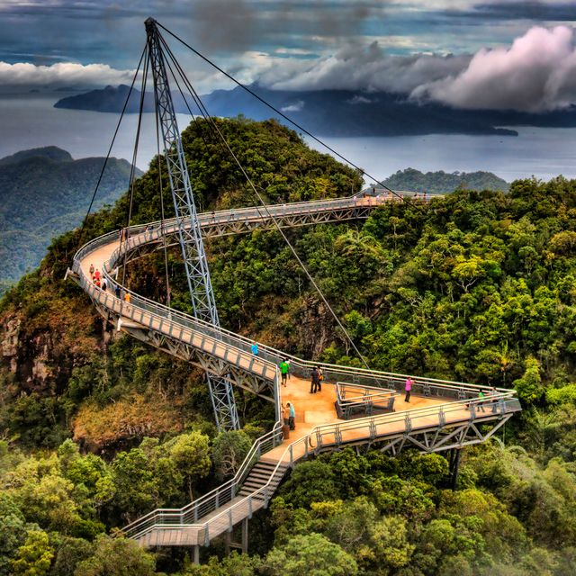 Malaysia  Langkawi Sky Bridge is a curved pedestrian bridge 2000 feet above sea level at the top of Mount Mat Cincang in Malaysia. Tourists who want to walk across the 400-foot long structure must ride up to it in a cable car. The deck is less than 6 feet wide and its curved shape gives travelers a panoramic view of Langkawi, an archipelago of 99 islands. Each end is fitted with triangular observation decks.