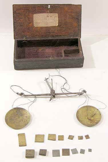 An early 19th century set of Apothecarys' Drug Scales, hand held by the cotton tag, in it's original case and with a set of Drachm weights. The steel beam balance has brass pans suspended by cotton threads and the whole instrument and weights fit into the six inch long oak chest type case with working catch & hinges