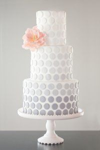 Ombre applique dots in shades of grey with an open ruffle sugar peony are featured in this cake.