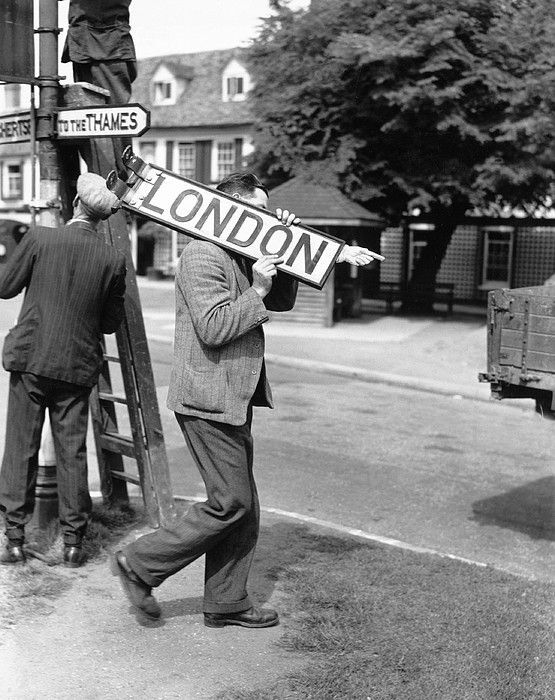 "A "" To London"" sign being removed from a signpost in a Surrey village to ensure that no help is given to any possible invader in WW2."