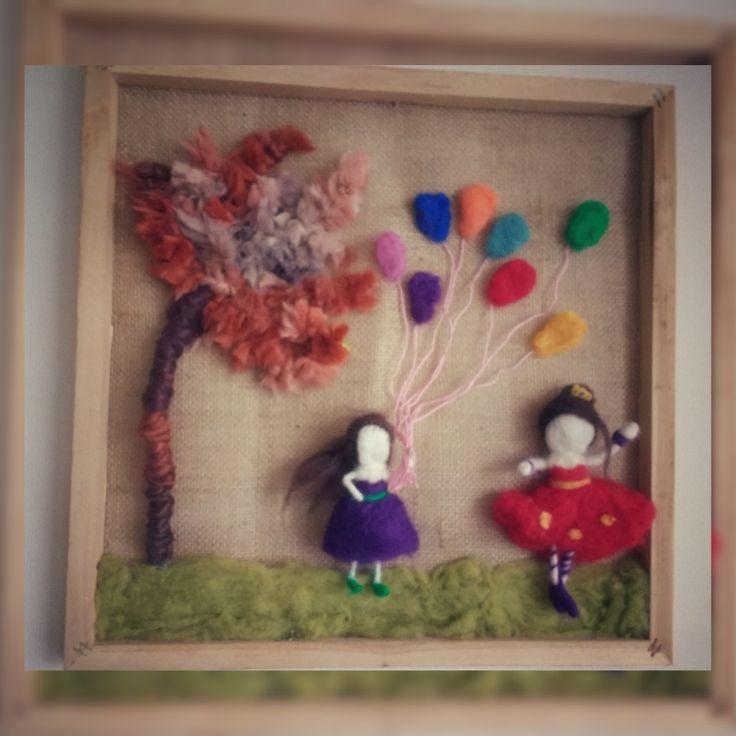 Cuadro de madera natural con fondo de arpillera, árbol de lana, pasto, muñecas y globos de fieltro agujado $20.000 clp