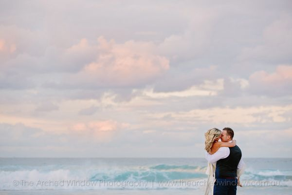 bride and groom against the ocean waves and sky during sunset. Photography by The Arched Window.