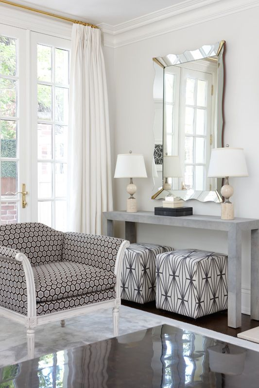 Contrasting monochromatic graphic fabrics, on armchair, and box stools.