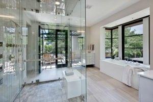 Ein zeitgenössisches Design Badezimmer mit weißen Wanne, geschlossenen Duschraum, Holzböden und flat-Panel-Schränke für das Wesentliche. / Foto von Stocker Hoesterey Montenegro