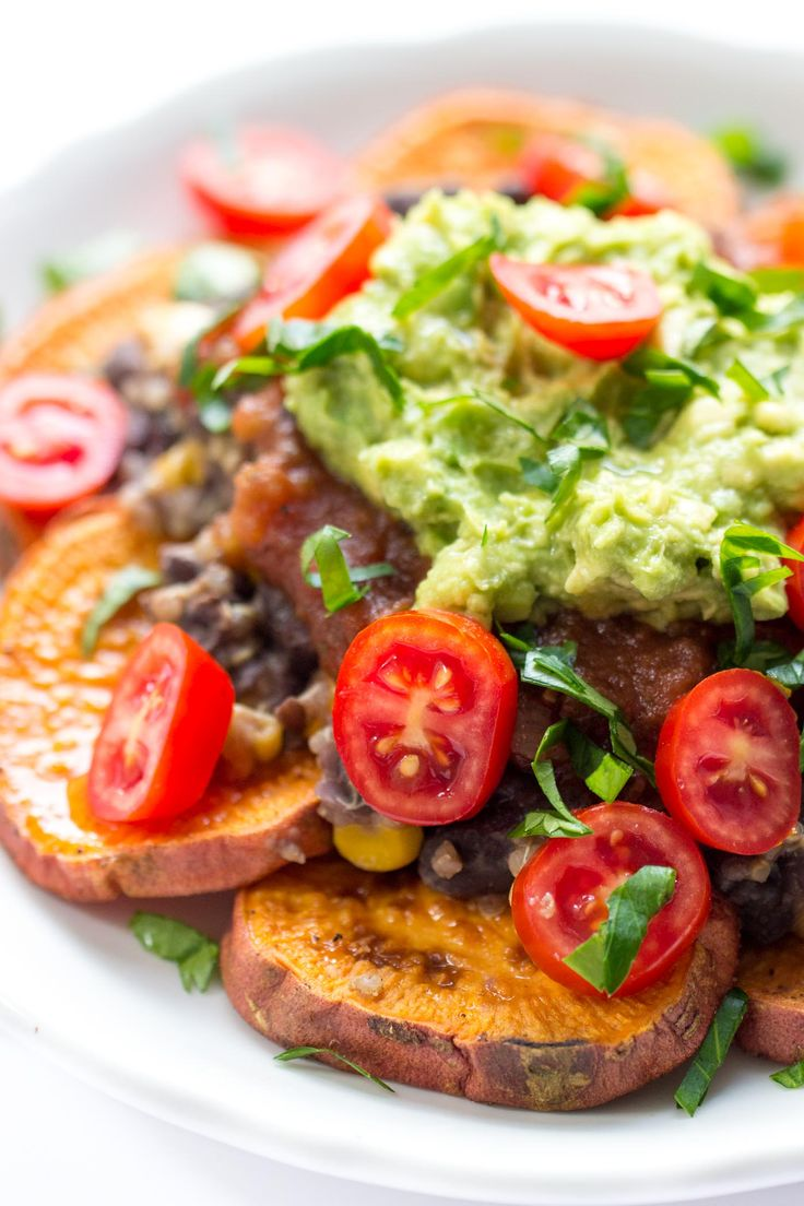 BEST vegan nachos on the planet!! Use sweet potatoes instead of corn chips, skip the meat and add black beans + quinoa, then top it all off with salsa, guac and cilantro. PERFECTION!