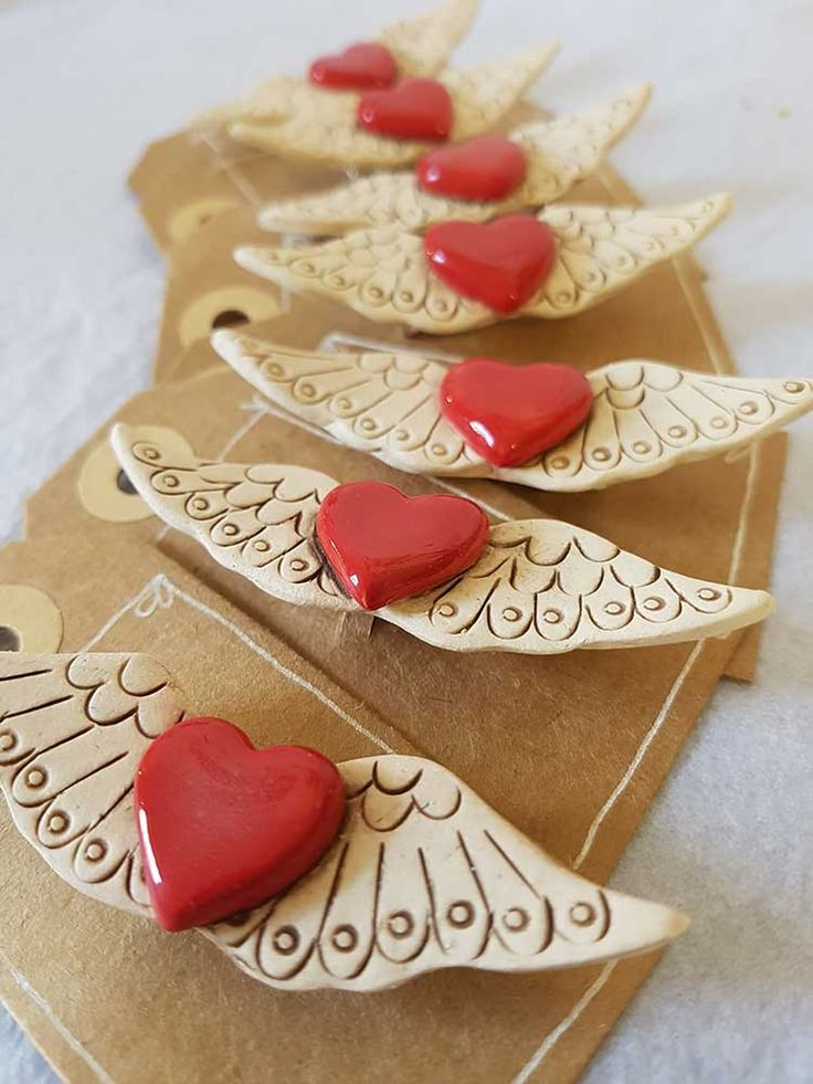 A handmade ceramic brooch, with a brooch pin set on the reverse. This fluttering heart brooch has surface decoration over the wings, and a glossy glazed red heart nestled in the middle. A loving gift for yourself, or someone else...