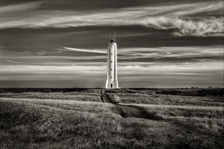 A lighthouse stands, strong and alert, at the edge of a field in rural Iceland.