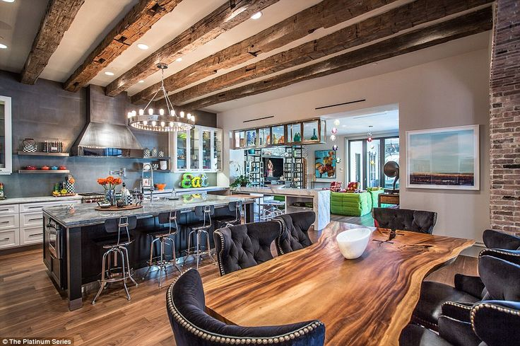 The open-plan kitchen and dining area has plenty of room for entertaining guests and features wooden beams across the ceiling