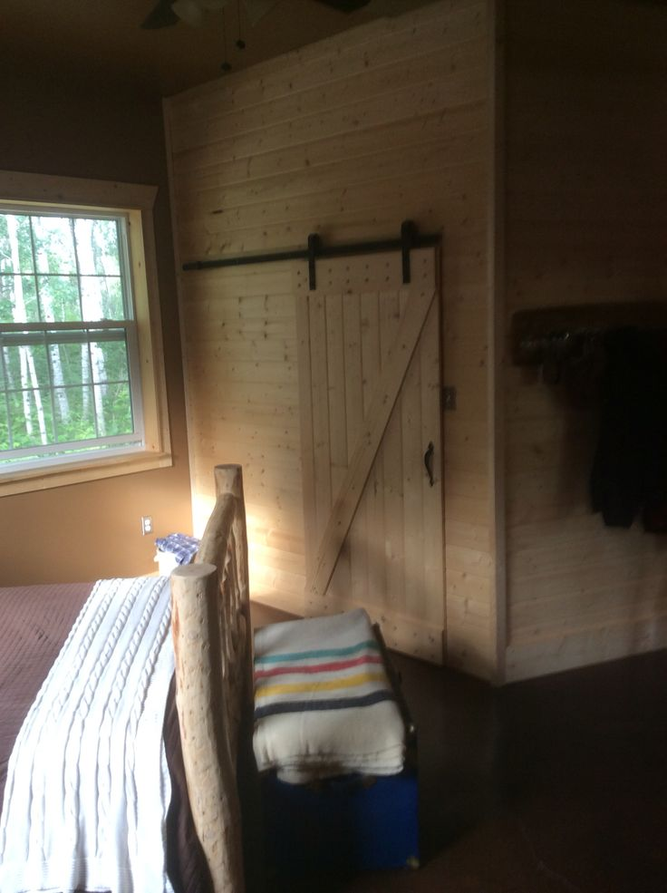 Sliding barn door made with knotty pine & black hardware. The handle is from an exterior gate.