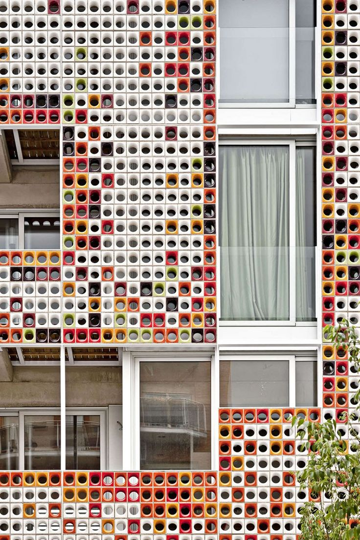 Lagula Architects gave this apartment building in Badalona, Spain, a facade made of glazed ceramic blocks in a variety of colors.