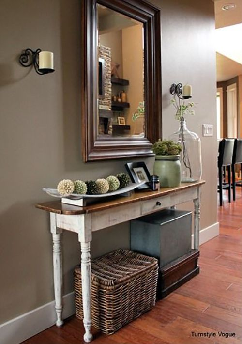 La peinture blanche usée de la console cède la place à un dessus en bois parfaitement remis en état.Le grand miroir au-dessus de la console rend l'espace beaucoup plus grand qu'il n'y parait. Les bougies de chaque côté sont une excellente idée de décoration.
